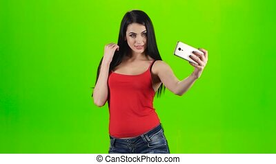 Brunette girl making selfie photo using a smartphone. Green...