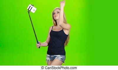 Blonde girl makes various photos using selfie stick. Green...