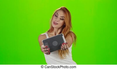 Redheaded model grimaces on camera a tablet. Green screen...