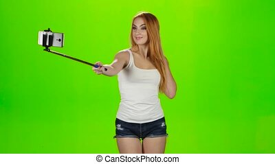 Redheaded girl makes various photos using selfie stick....