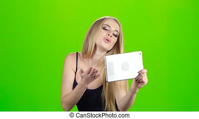 Blonde girl makes various photos using camera of tablet pc,...