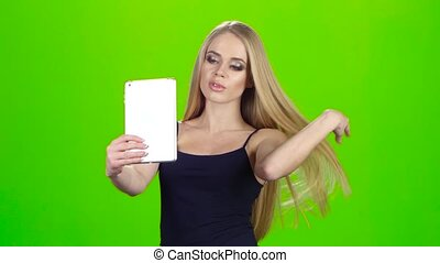 Photo using the front camera of tablet. Selfie blonde girl