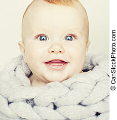 little cute red head baby in scarf all over him close up...