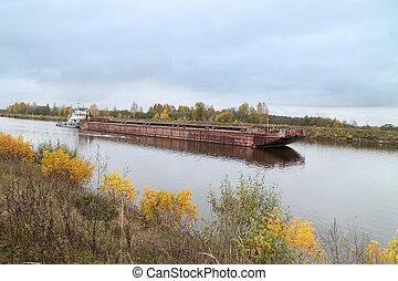 tugboat pushs barge under a river