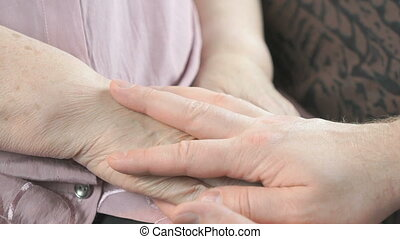 Man holding old wrinkled hands of elderly woman - Man...