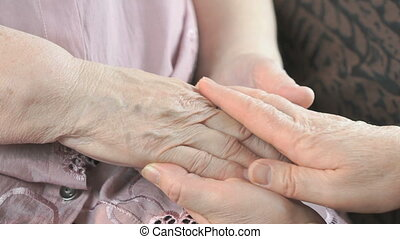 Woman holding flabby wrinkled hands of old woman - Woman...