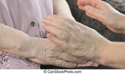 Woman soothes elderly woman during stress - Woman holding...