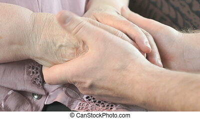 Man soothes elderly woman during stress - Man holding the...
