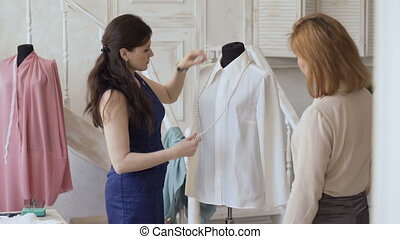 Young clother designer woman shows final result to her client in tailor studio