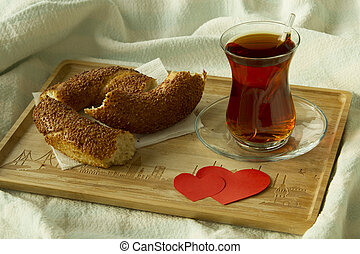 Morning turkish tea in traditional glass with bagel on the tray with two red hearts, breakfast in bed