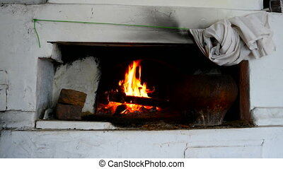 Fire is burning in a rustic wood stove. Flame heats the rural farmhouse