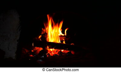 Fire is burning in a rustic wood stove. Flame heats the...