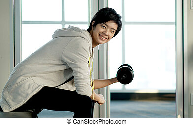 Sporty look Asian woman lifting dumbbells and smiling in gym
