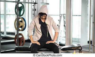 Asian sportwoman wearing hood tiring and resting after...