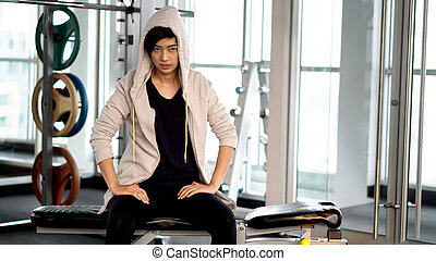 Asian sportwoman wearing hood resting after exercise at gym...