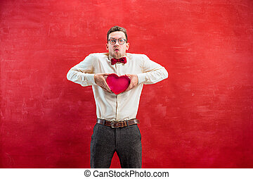 Young beautiful man with abstract heart on red studio...