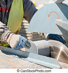 Circular saw - Construction worker cutting plastic pipe on a...
