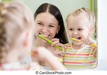 Mother And Kid Daughter Brushing Teeth Together In Bathroom...