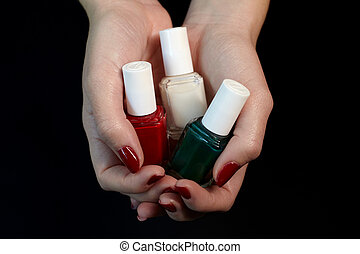 Polish bottles in woman hands.