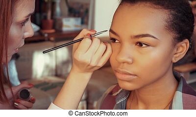 Makeup artist paints the eyebrows of a young beautiful...