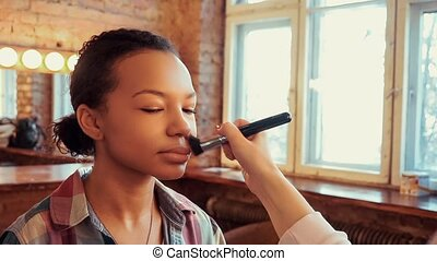 Make-up artist doing make up for young pretty mulatto girl