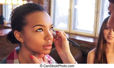 Make-up artist doing make up for young beautiful girl