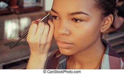 Make up artist doing make up using profesional makeup brush.