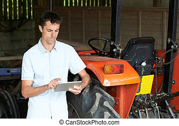 Farmer Standing Next To Tractor Using Digital Tablet