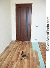 Laminate flooring installation interior. Installing wooden laminate flooring.