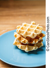 Homemade waffles on blue plate - Three fresh homemade...