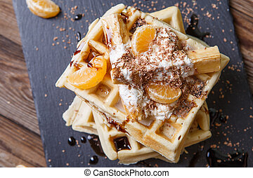 Black board with Belgian waffles with tangerines and...