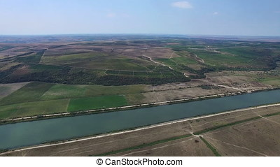 Aerial flight above green meadows and Danube river