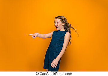 The surprised teen girl with long hair pointing on orange...