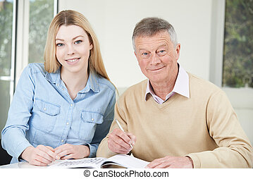 Senior Man Playing Completing Crossword Puzzle With Teenage Granddaughter