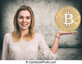 Woman showing Golden Bitcoin coin. Cryptocurrency -...