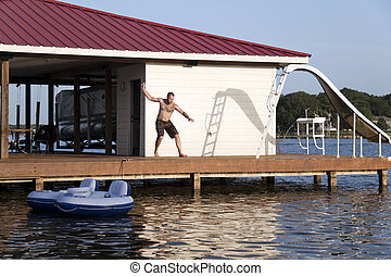 Man Flipping - A man is doing a back flip off the end of a...