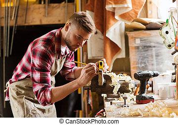 carpenter with ruler measuring plank at workshop -...