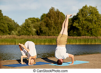 couple making yoga outdoors - fitness, sport, yoga, people...