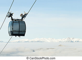 Cable car cabin going up above the clouds to the very top of...