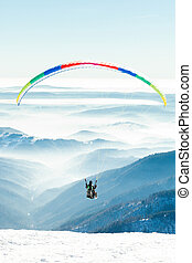 Paragliders launched into air from a snowy slope of a...