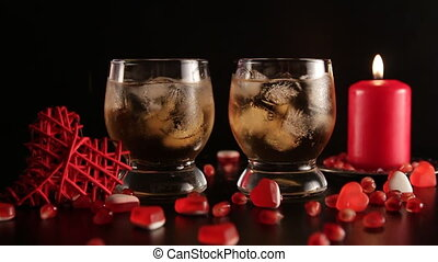 Confetti falling down slow motion. Two glasses with alcohol decorated with candies, red candle, closeup. Romantic still life isolated on black background. Saint valentine's day celebration. Long shot.