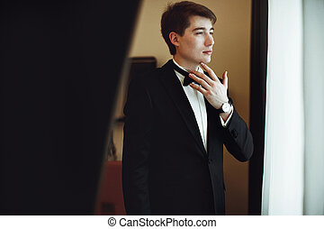 Groom looks thoughtful standing behind a window in a hotel room