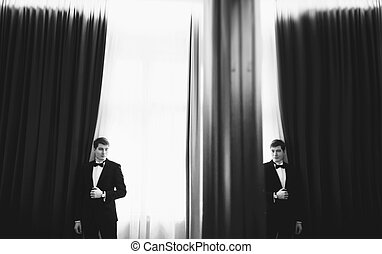 A reflection of a groom in the mirror