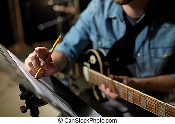 man with guitar writing to music book at studio - people,...