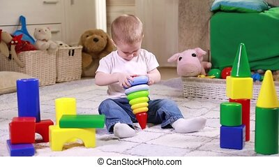 Little boy playing with color blocks - Little boy playing...