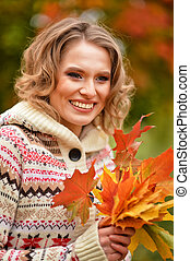 blonde woman with autumn leaves posing outdoors