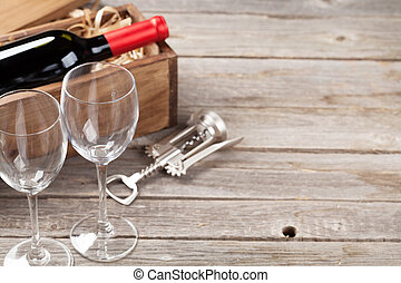 Red wine bottle and glasses on wooden table. View with copy...