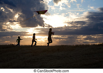 Family runs with a kite.