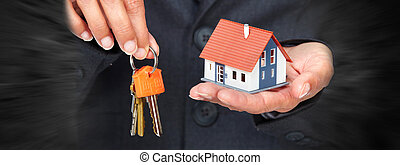 Hand with a little house and keys. - Hand with a small house...