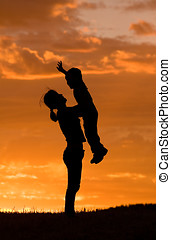 Mother holds son up. - A mother holds her little sun up in...